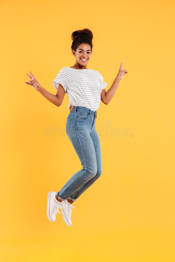 Funny african joyful lady jumping and smiling isolated royalty free stock photos