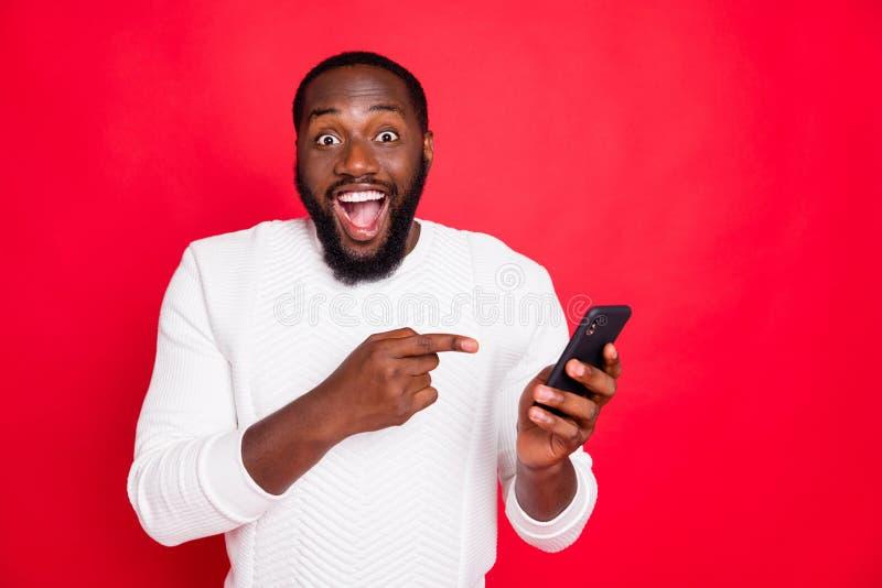 Photo of funny dark skin man holding telephone advertising new model smart phone indicating finger advice low price wear. Photo of funny dark skin man holding stock image