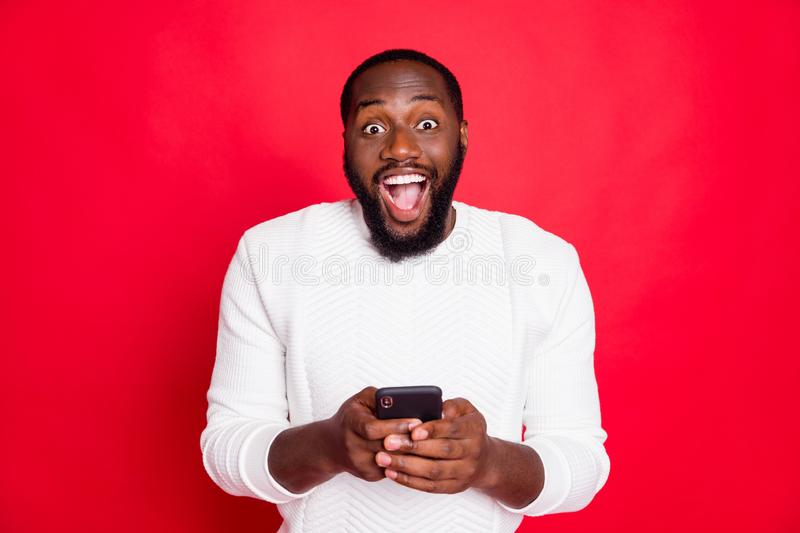 Photo of funny dark skin man holding telephone hands reading new x-mas comments in blog wear white knitted sweater. Photo of funny dark skin man holding stock photography