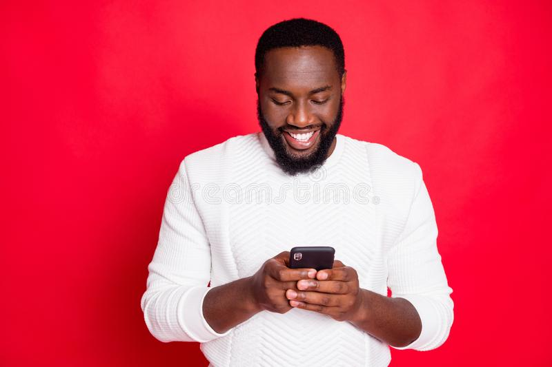 Photo of funny dark skin man holding telephone hands reading new x-mas comments in blog wear white knitted sweater. Photo of funny dark skin man holding royalty free stock photography
