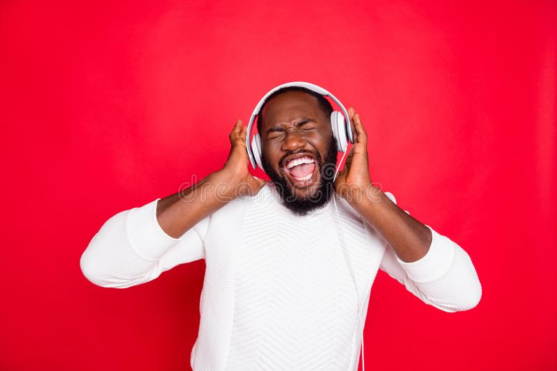 Photo of funny dark skin man listening to favorite playlist in earflaps crazy singing cool track wear white knitted. Photo of funny dark skin man listening to stock images