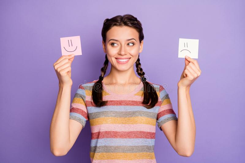 Photo of funny lady holding paper emoticons good and bad mood picking positive emotions wear casual striped t-shirt. Photo of funny lady holding paper emoticons stock photography