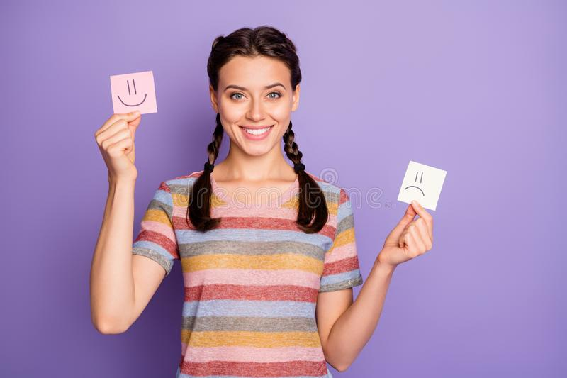 Photo of funny lady holding paper emoticons good and bad mood recommending positive emotions wear casual striped t-shirt. Photo of funny lady holding paper stock photos