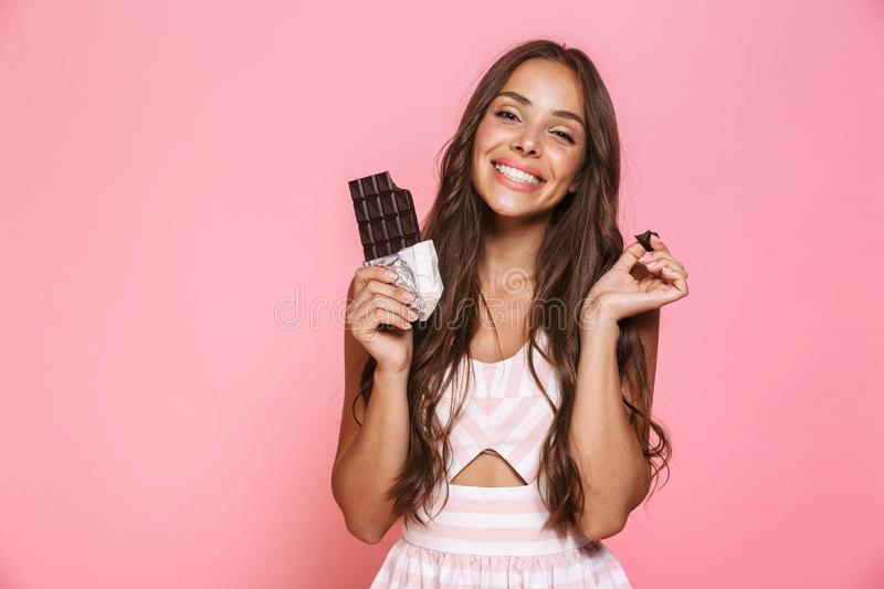Photo of funny woman 20s wearing dress smiling and eating chocolate bar, isolated over pink background stock image