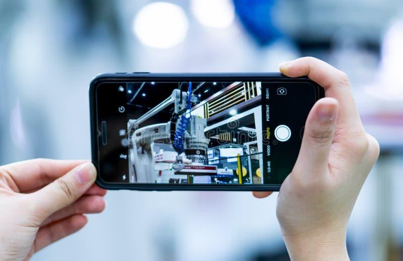 Photo futée de pousse de téléphone d'utilisation de main de femme de robot à l'expo industrielle Traitement d'International et év images stock