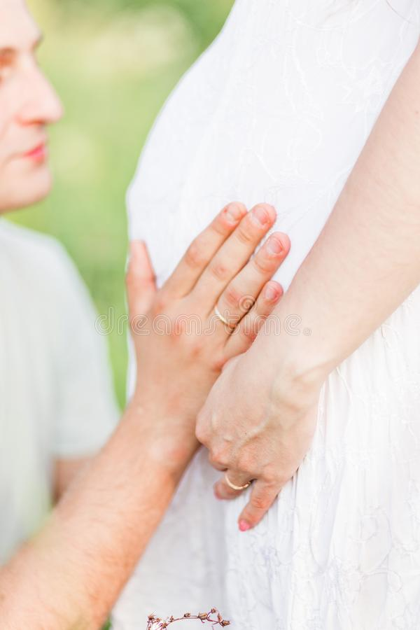 Future father hugs and kisses his wife`s pregnant belly. Photo of Future father hugs and kisses his wife`s pregnant belly stock photography
