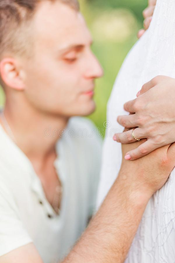 Future father hugs and kisses his wife`s pregnant belly. Photo of Future father hugs and kisses his wife`s pregnant belly royalty free stock images