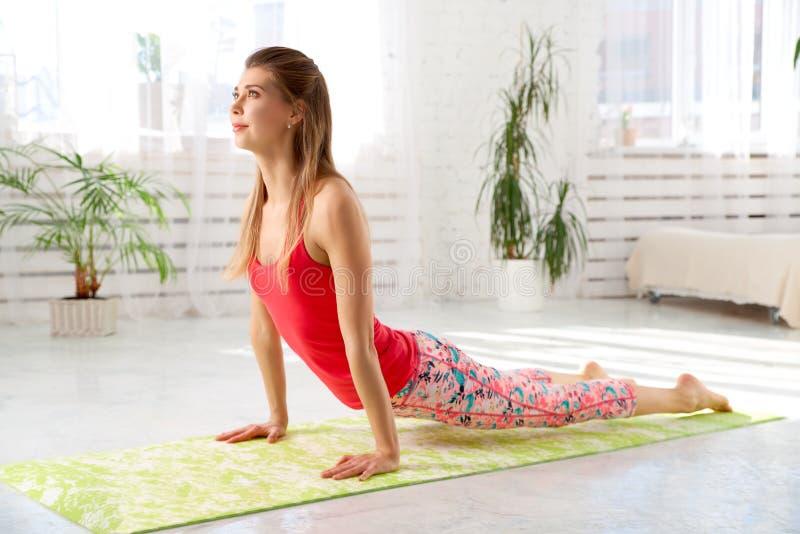 Photo gentille de beau yoga de pratique femelle Femme méditant faisant la pose de cobra Intérieur blanc avec la grande fenêtre photos stock