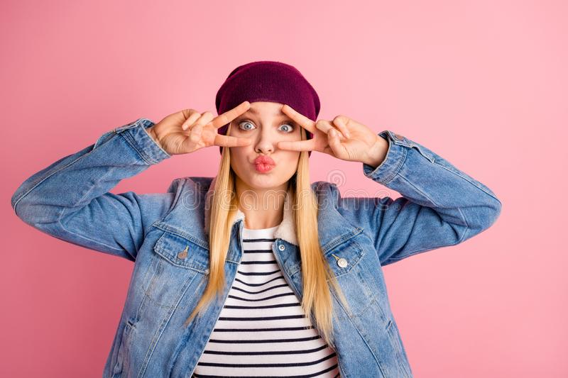 Photo of gesturing fooling teenager staring at camera objective showing v-sign while isolated with pink background. Photo of gesturing fooling teenager, staring stock photography