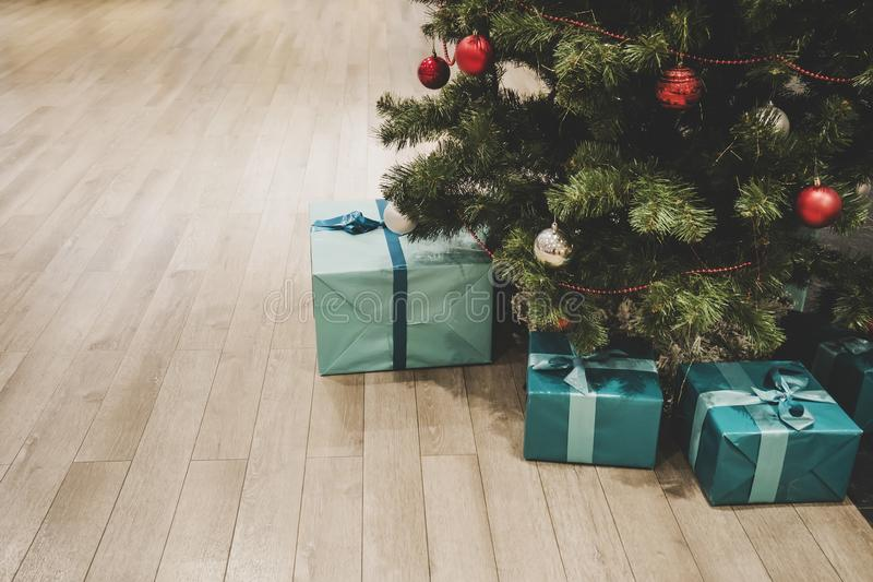 Photo of gift boxes under Christmas tree, New Year home decorations, wrapping of Santa presents, festival fir tree decorated with royalty free stock photography
