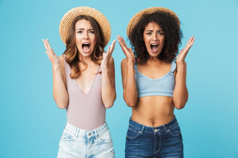 Photo of ginger caucasian and african american women wearing straw hats and swimsuits screaming in outrage and raising. Arms isolated over blue background stock photography