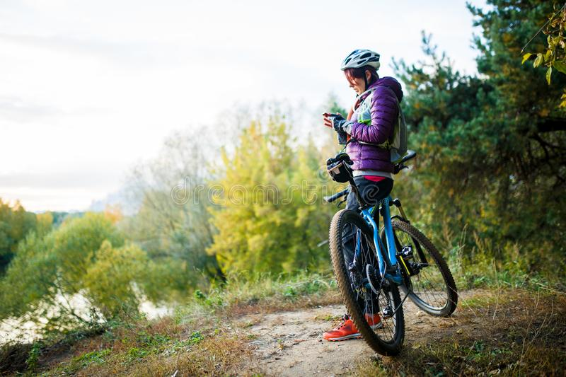Photo of girl in helmet standing with phone in hands near bicycle stock photography