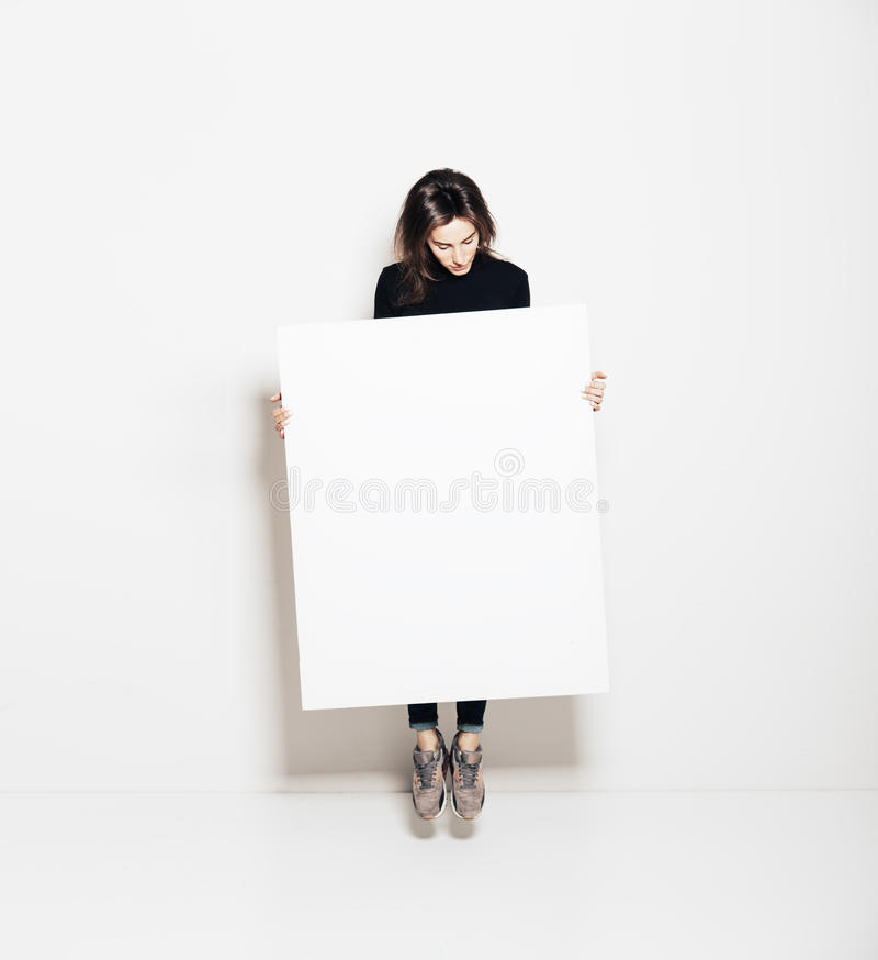 Photo of girl jumping in modern gallery and looking at the blank white canvas. Horizontal, mockup stock images