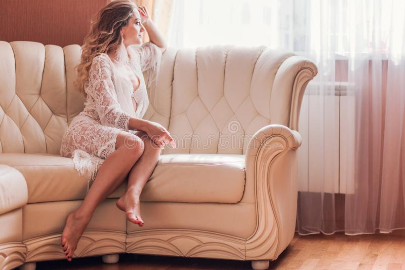 Girl in peignoir sitting on the couch in the room royalty free stock photography