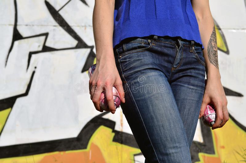 Photo of a girl`s hand with aerosol paint cans in hands on a graffiti wall background. The concept of street art and use of aerosol paints. Graffiti art shop royalty free stock photo