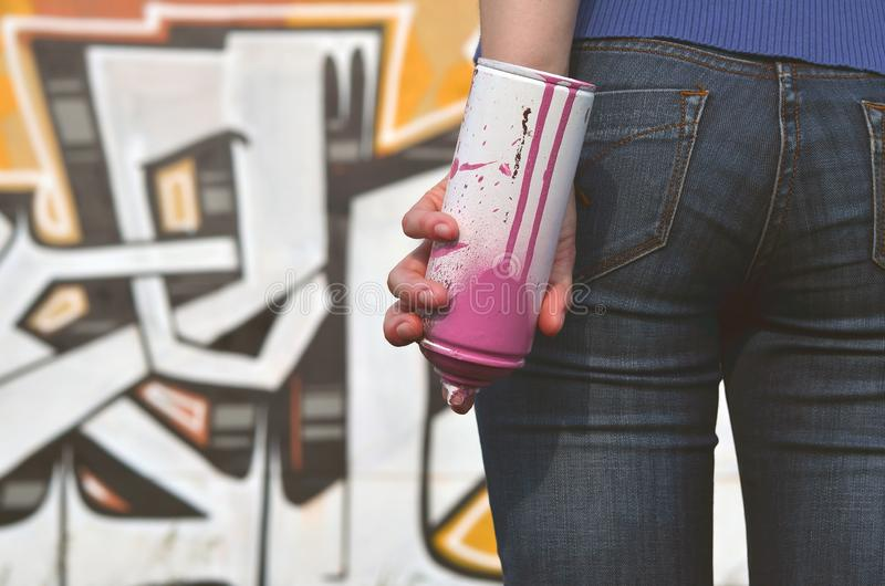 Photo of a girl`s hand with aerosol paint cans in hands on a graffiti wall background. The concept of street art and use of. Aerosol paints. Graffiti art shop stock photo