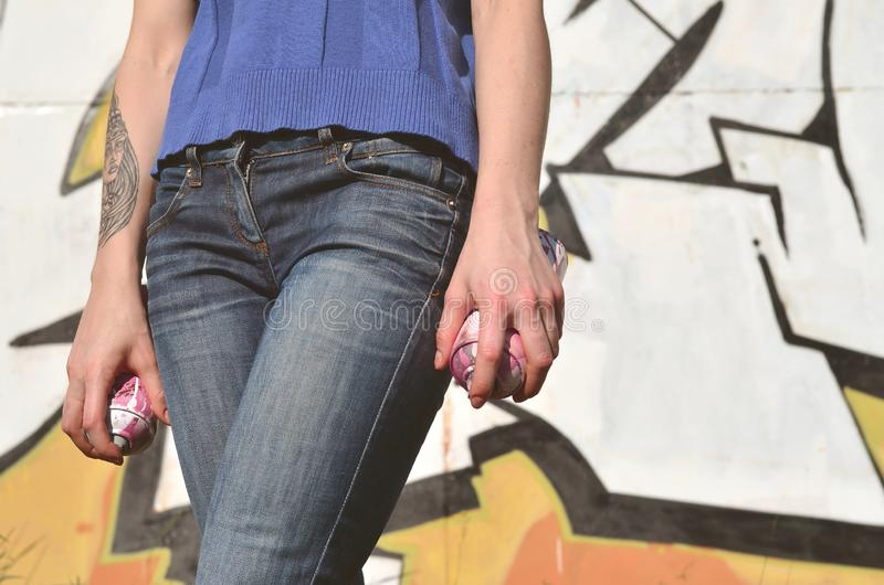 Photo of a girl`s hand with aerosol paint cans in hands on a graffiti wall background. The concept of street art and use of. Aerosol paints. Graffiti art shop royalty free stock image