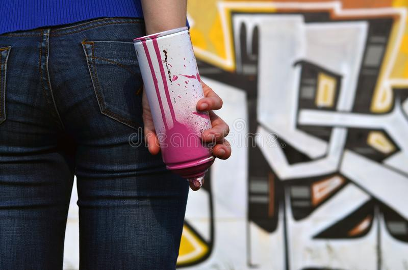 Photo of a girl`s hand with aerosol paint cans in hands on a graffiti wall background. The concept of street art and use of aerosol paints. Graffiti art shop stock image