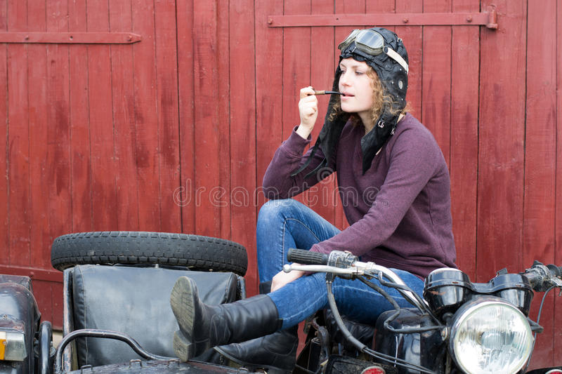 Photo of girl on a vintage motorbike in pilot cap with smoking pipe. Photo of girl on vintage motorbike in pilot cap with smoking pipe stock image