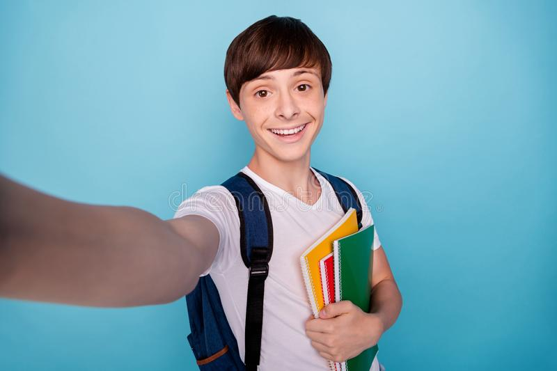 Photo of glad nice school boy photographing himself on his way to school while isolated with blue background stock photos