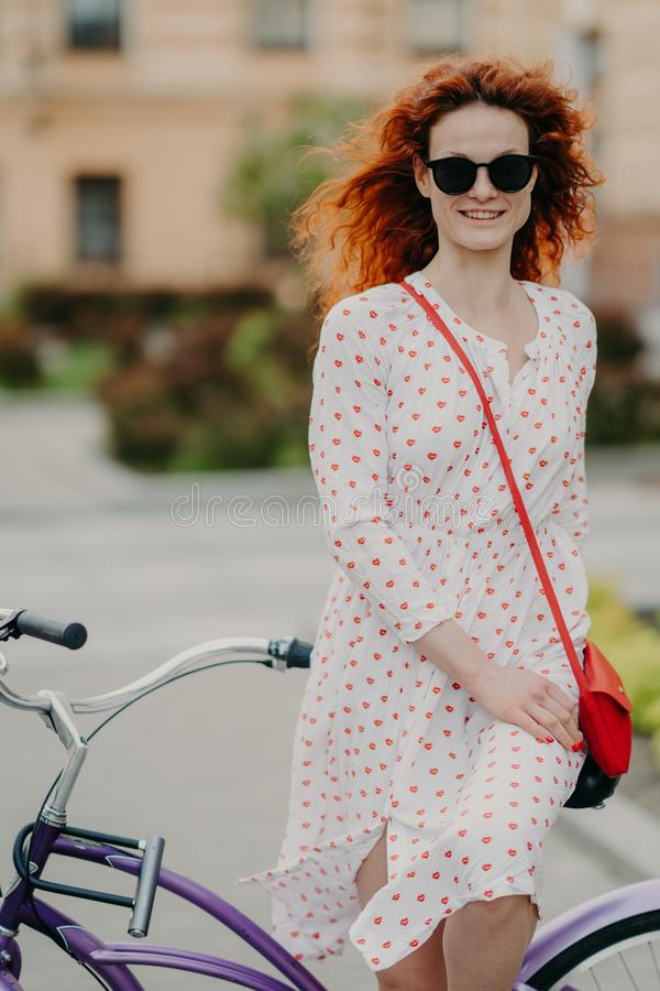 Photo of glad red haired woman with gentle smile, spends leisure time riding bicycle on city streets during sunny windy day, wears royalty free stock images