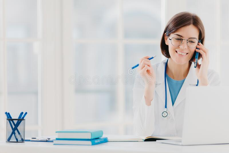 Photo of glad woman therapist or physician has phone conversation with patient, gives advice how to cure disease, wears white gown. Reads information on laptop royalty free stock photos