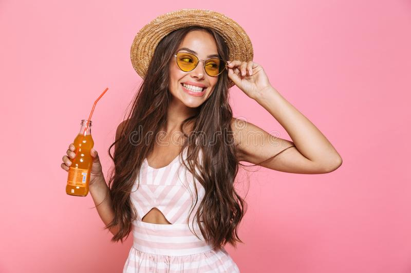 Photo of glamour woman 20s wearing sunglasses and straw hat drinking lemonade from glass bottle, isolated over pink background royalty free stock images