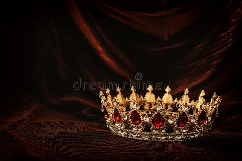 Photo of gold crown over gothic dark silk background. Medieval period concept. Photo of gold crown over gothic dark silk background. Medieval period concept stock image