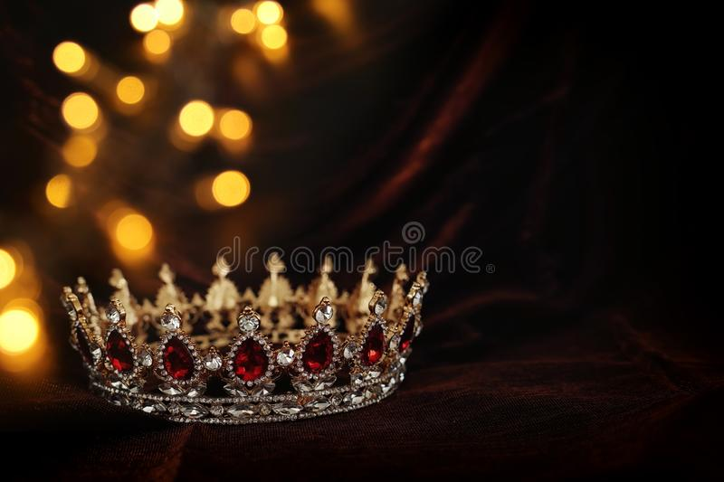 Photo of gold crown over gothic dark silk background. Medieval period concept. Photo of gold crown over gothic dark silk background. Medieval period concept stock photo