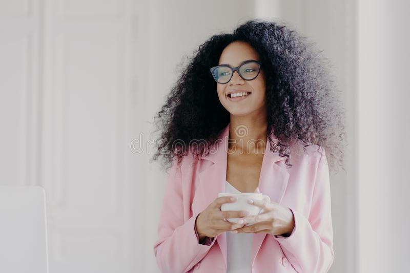 Photo of good looking African American prosperous busineswoman waits for partner in office, drinks coffee discusses future plans. With colleague looks away with stock image