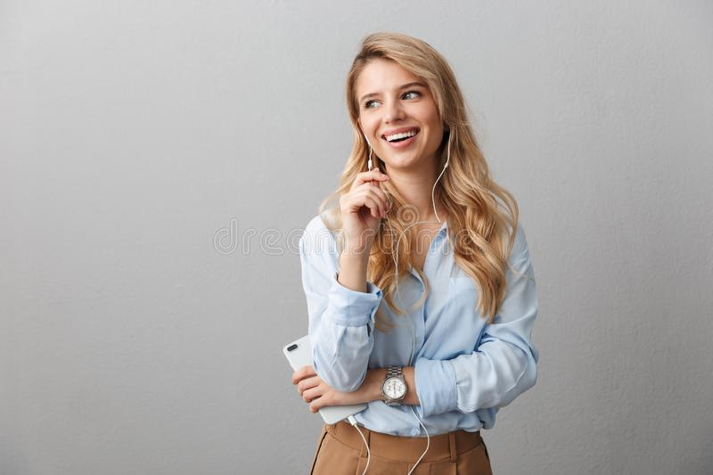 Photo of gorgeous blond businesswoman with long curly hair rejoicing while listening to music with smartphone and earphones. Over gray background royalty free stock images