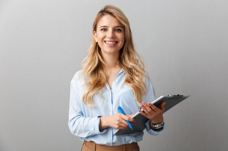 Photo of gorgeous blond secretary woman with long curly hair writing down notes in clipboard while working in office. Isolated over gray background royalty free stock image