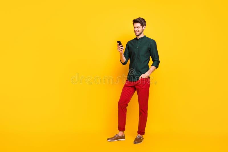 Photo grandeur nature de l'homme gai positif s'amuser pendant les vacances de printemps utiliser son smartphone taper post commen photographie stock libre de droits