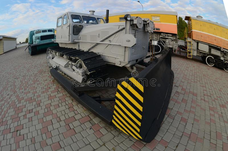 Photo of a gray bulldozer among the railway trains. Strong distortion from the fisheye len royalty free stock photography