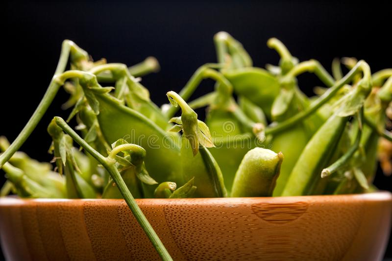 Photo of green pea pods in wooden cup on blank black background in royalty free stock image