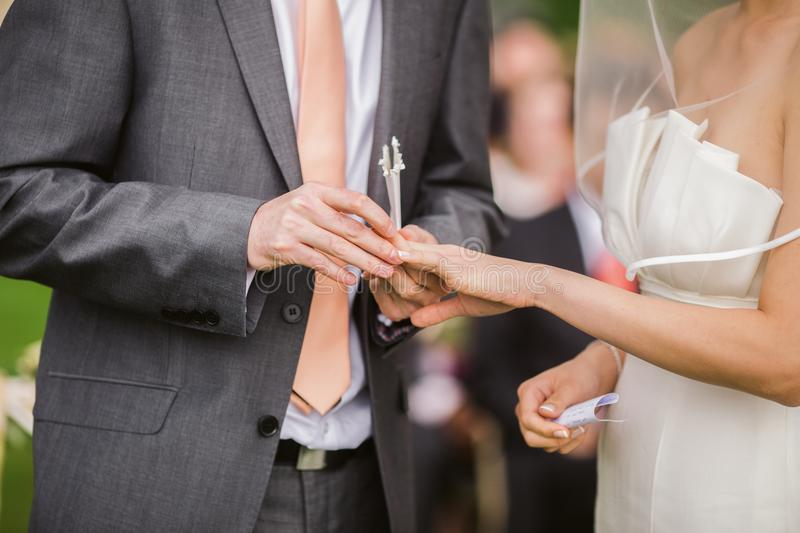 Photo of Groom Putting Wedding Ring on His Bride royalty free stock images