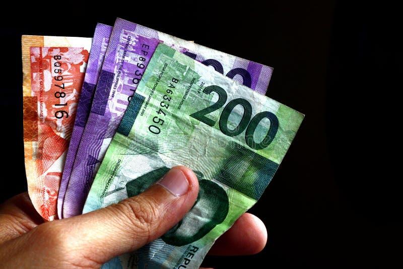 Hand holding Philippine peso bills. Photo of hand holding Philippine peso bills stock images