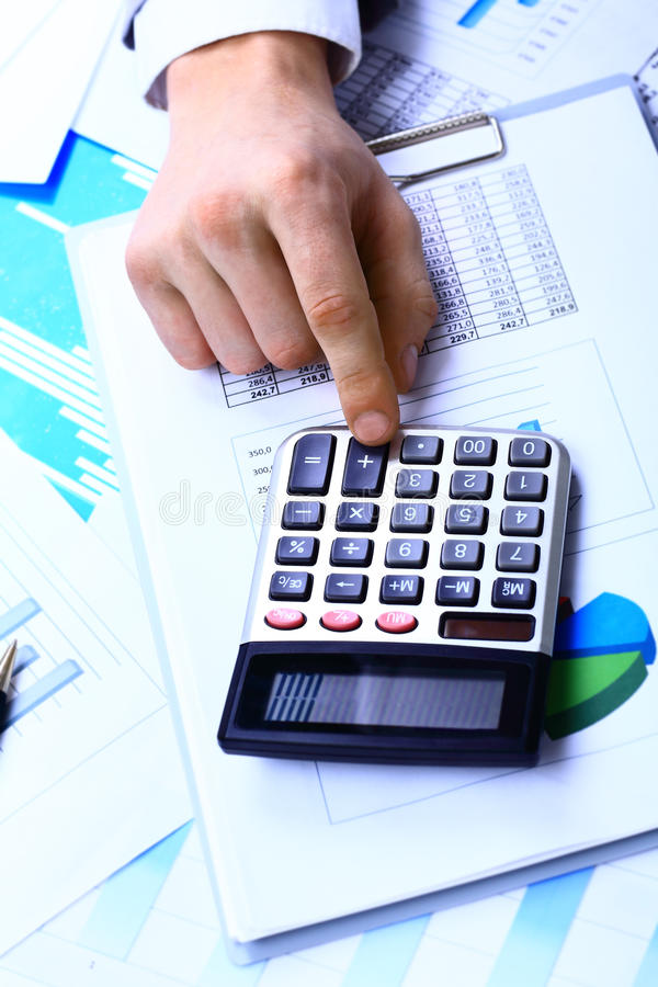 Photo of hand pressing calculator buttons stock image