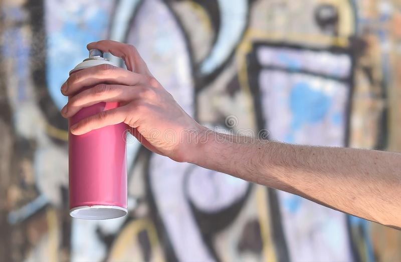 Photo of the hand of a street artist who draws a new color pictu. Re on a brick wall. One of the types of street art is the culture of youth graffiti. Decoration royalty free stock photography