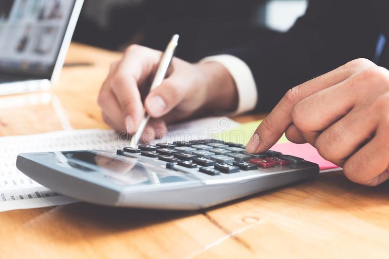Photo of hands holding pen and pressing calculator buttons over stock images