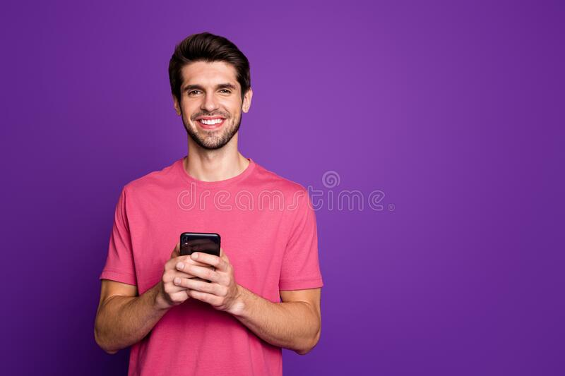 Photo of handsome attractive guy young millennial hold telephone hands popular blogger addicted user wear casual pink t. Photo of handsome attractive guy young royalty free stock photos