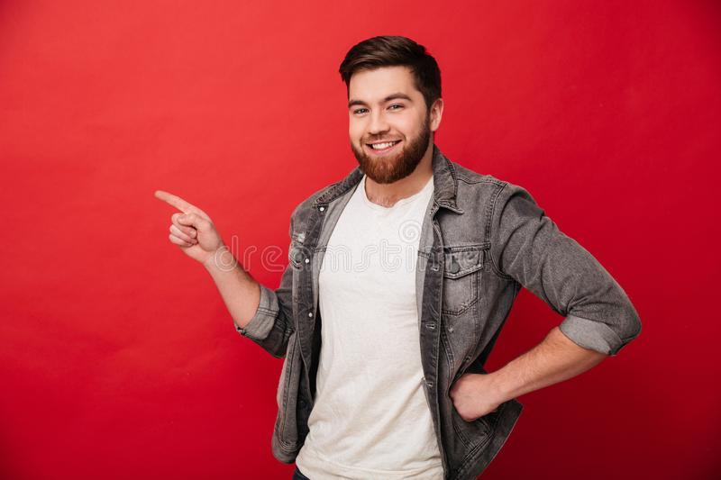 Photo of handsome cheerful man 30s in jeans jacket gesturing fin. Ger aside on copyspace with gladness on face isolated over red background royalty free stock photography