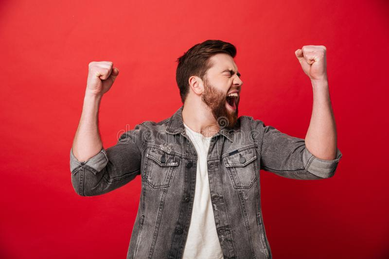 Photo of handsome cheerful man 30s in jeans jacket screaming and. Clenching fists in joy isolated over red background stock photography
