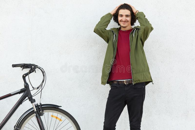Photo of handsome content unshaven guy looks with positive expression at camera, keeps hands on head, wears fashionable jacket, st royalty free stock photo