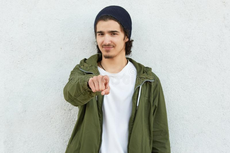 Photo of handsome guy points with index finger at camera, expresses his choice, dressed in green anorak and black headgear, focus royalty free stock photography