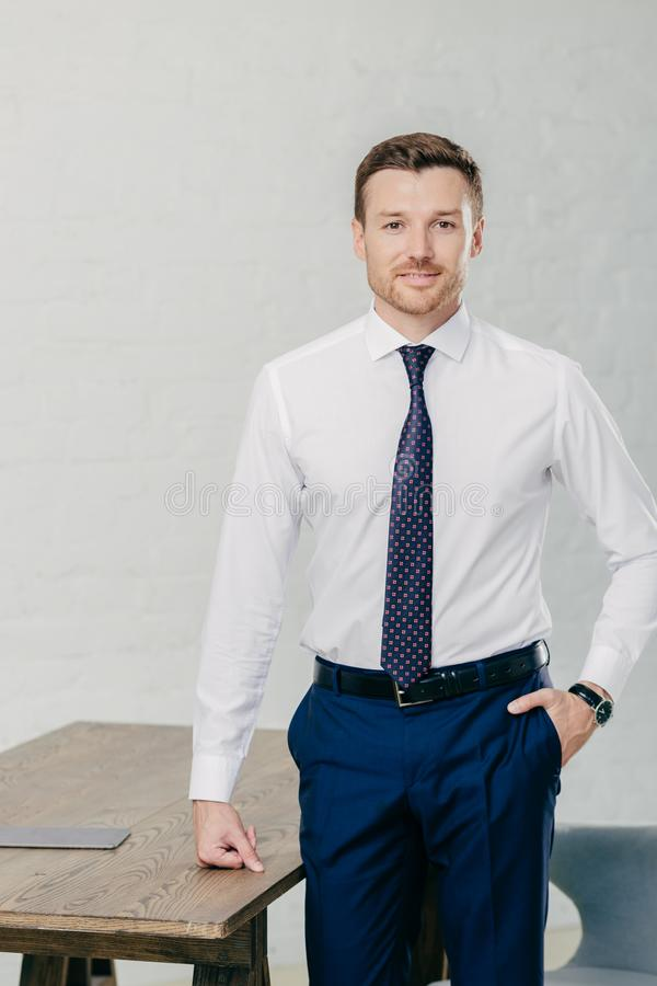 Photo of handsome male office worker dressed in formal clothes, keeps one hand in pocket, other on table, looks confidently at cam stock photos