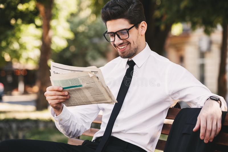 Photo of handsome man in businesslike suit sitting on bench in g. Reen park and reading newspaper during sunny day royalty free stock images