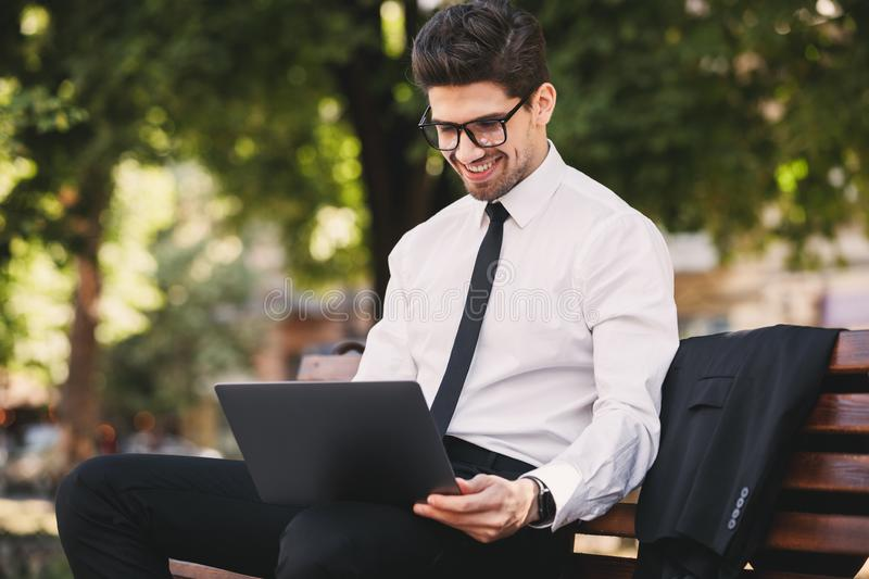 Photo of handsome man in businesslike suit sitting on bench in g. Reen park and working on laptop during sunny day royalty free stock image