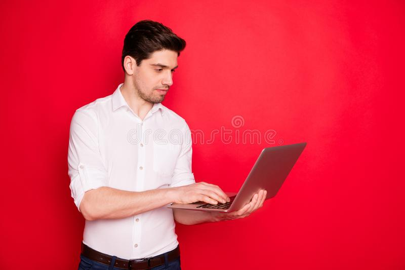 Photo of handsome man freelancer working with laptop searching for some information while isolated with red background. Photo of handsome, man freelancer working stock photography