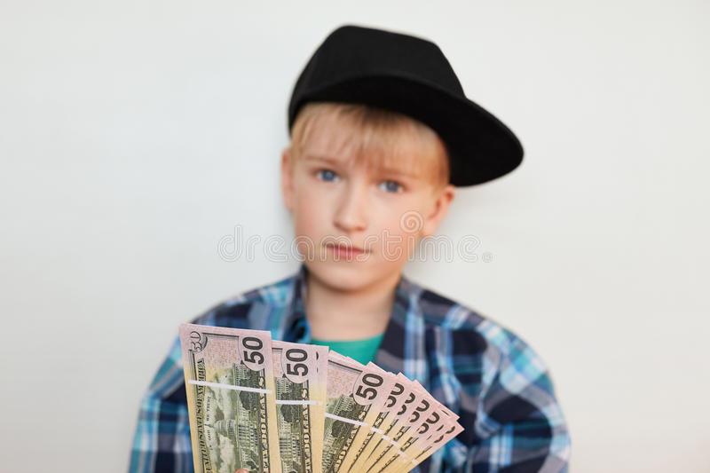 A photo of handsome stylish liitle rich child dressed in black cap and modern shirt holding dollars in his hands. Young businessma stock photography